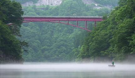 遠望福島縣奧會津的霧幻峽的只見川上泛舟的人力小舟船家在橋下泛舟