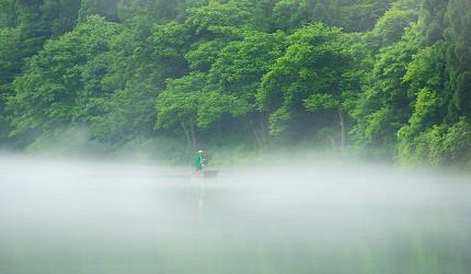 遠望福島縣奧會津的霧幻峽的只見川上泛舟的人力小舟船家在樹旁泛舟